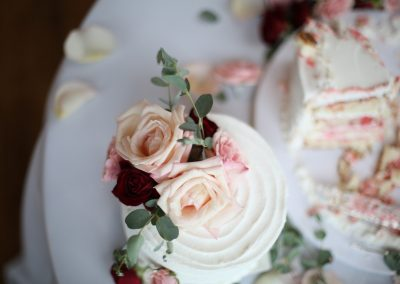 Messy Wedding Cake that Has Already Been Sliced with Roses