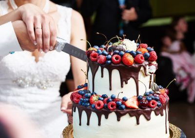 Cutting the wedding cake with berries